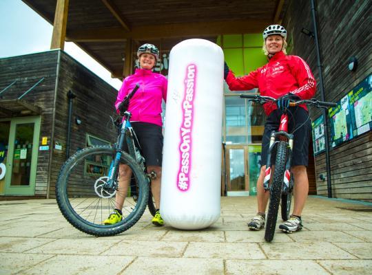Giant baton being handed to female Mountain bike coach