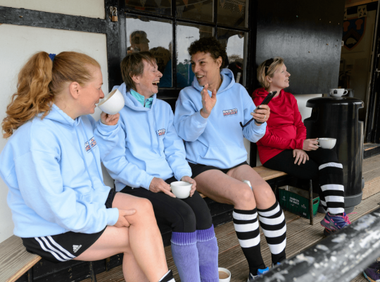 four women talking before a hockey game on a bench