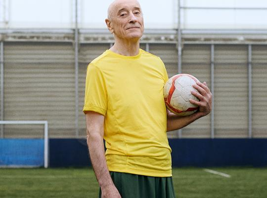 An older male holding a football
