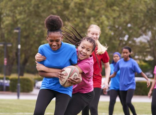 Teenage in red T-shirt tackling girl in a blue t-shirt,  laughing whilst playing ruby in green open space. Hair flying behind them