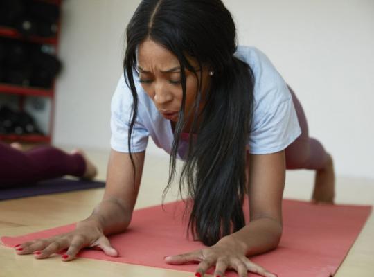 female doing yoga inside
