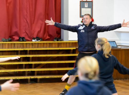 male teacher doing star jumps with with a class on young people