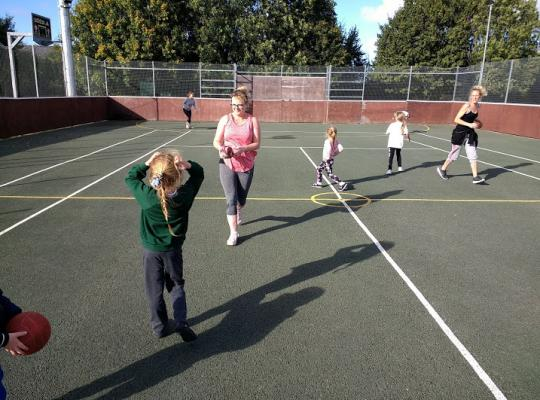 families enjoying activities on a multi use court