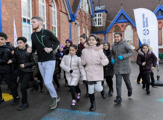 Group of children running in school uniform with their teacher around a playground