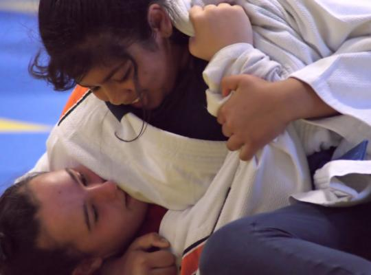 two girls competing in a judo match