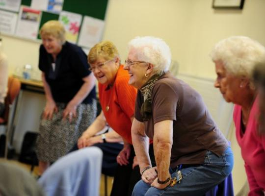 a group of older females laughing whilst doing some standing exercises indoors in a circle