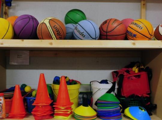 diffrent coloured sports equipment in a cupboard