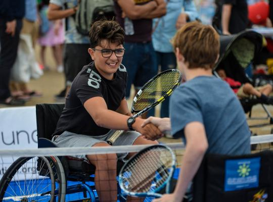 Two wheelchair players shaking hands over the net