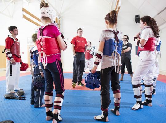 Taekwondo coach talking to group of participants